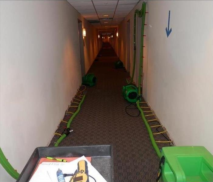 Drying a hallway after a storm caused water damage
